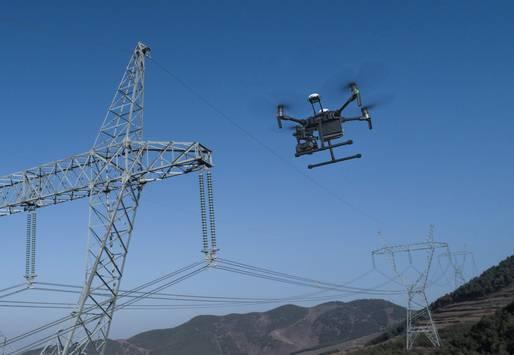 Drohne bei der Inspektion von Stromleitungen