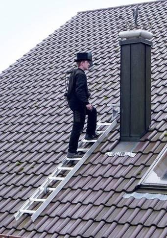 Schornsteinfeger auf Dach mit einer Leiter
