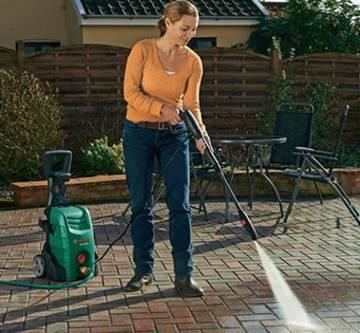 Frau reinigt Steinboden mit Hochdruckreiniger